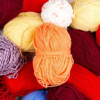 Flatlay de pastel multicolorido tricô meadas de fios e agulhas de tricô em fundo branco