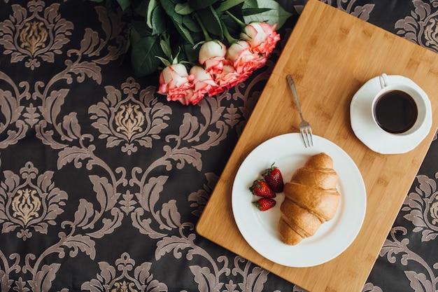 Flatlay de rosas croissant e café em uma textura bonita.