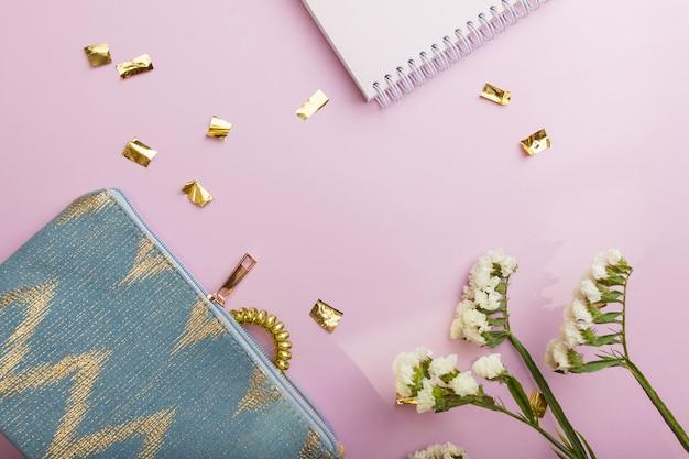 Flatlay de saco cosmético e flores sobre fundo violeta. lugar para o seu texto. copyspace.