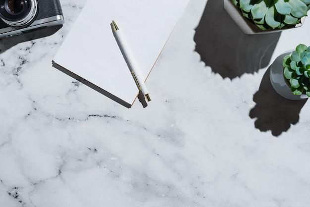 Flatlay de suculentas, câmera de filme vintage e caderno com caneta no mármore