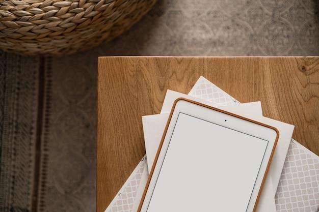 Flatlay de tablet pad de tela em branco, folhas de papel na mesa de madeira e tapete. área de trabalho da mesa do escritório doméstico