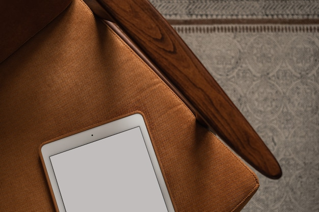 Flatlay de tablet pad de tela em branco na cadeira retrô e no tapete. área de trabalho da mesa do escritório doméstico