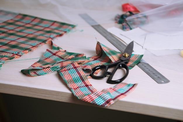 Flatlay de tecido xadrez cortado e tesoura em mesa de madeira: local de trabalho do alfaiate