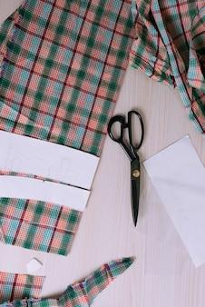 Flatlay de tecido xadrez recortado e tesoura na mesa de madeira: local de trabalho do alfaiate
