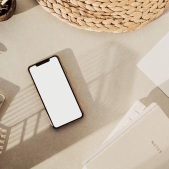 Flatlay de telefone inteligente de tela em branco, cadernos, clipes em uma tigela de madeira, suporte de palha em fundo de concreto bege.