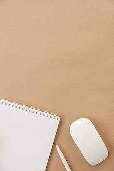 Flatlay do caderno em branco sobre fundo bege pastel. espaço de trabalho minimalista da mesa do escritório em casa. camada plana, vista superior