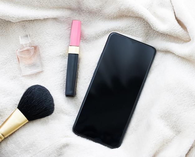 Flatlay feminino com perfume de batom para celular e maquete de smartphone para pincel de maquiagem como modelo de aplicativo ...
