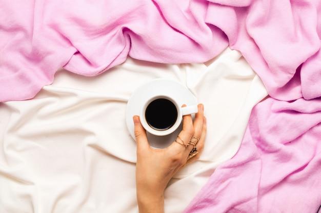 Flatlay lindo com a mão de uma mulher segurando uma xícara de café da manhã na cama. vista do topo