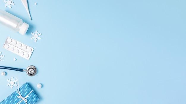 Flatlay médico de natal. copie o espaço. fundo azul. estetoscópio, termômetro, comprimidos, flocos de neve e bolas festivas. borda esquerda. equipamento médico.