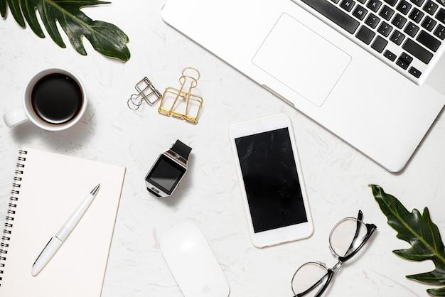 Flatlay no local de trabalho com notebook, laptop e xícara de café na mesa de mármore