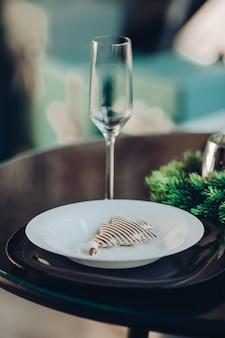 Flauta com dois pratos de porcelana branca e preta de diferentes tamanhos na mesa servida com ramo de abeto natural.