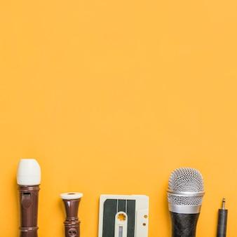 Flauta de bloco; fita cassete; microfone em fundo amarelo