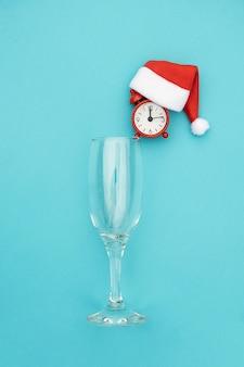 Flauta de champagne com despertador vermelho no chapéu de papai noel. conceito criativo natal ou ano novo bebendo tempo