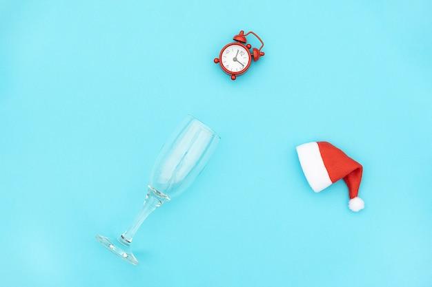 Flauta de champagne com despertador vermelho no chapéu de papai noel.