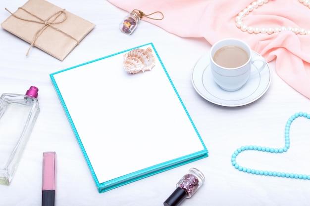 Flay lay da mesa do espaço de trabalho freelancer com espaço de cópia. café, papel em branco, brilho labial, jóias.