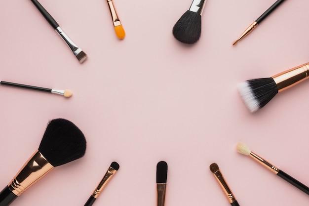 Flay lay moldura circular com pincéis de maquiagem e fundo rosa