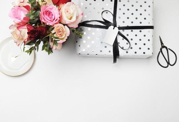 Flay leigos. as rosas brancas do ramalhete da tabela scissors o feriado festivo e branco dos bonsais da etiqueta.