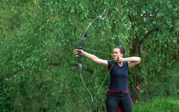 Flecha atirando de um arco na natureza, tiro com arco de esporte. copie o espaço