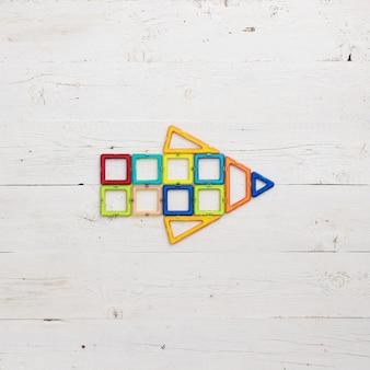 Flecha feita de peças de plástico magnéticas do construtor em um fundo branco de madeira