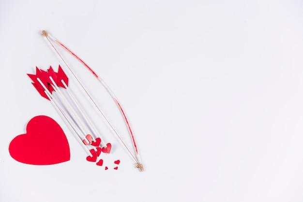Flechas de amor com arco e coração na mesa