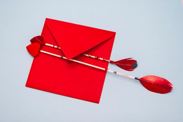 Flechas de amor com envelope na mesa cinza