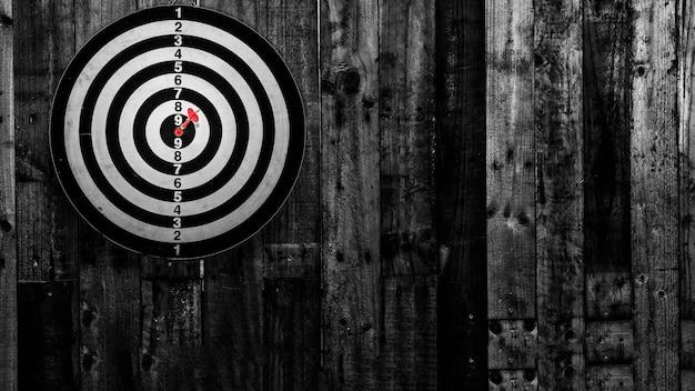 Flechas de dardos no centro alvo, luz a centro, fotografia em preto e branco.