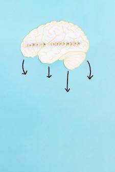 Flechas para baixo que caem do cérebro branco com blocos de brainstorming contra o fundo azul