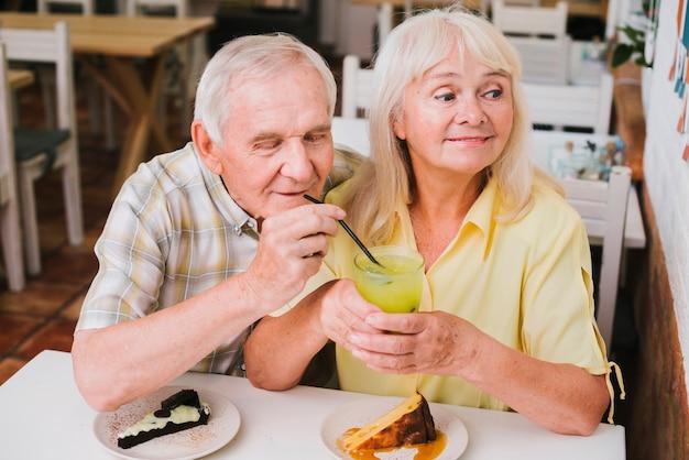 Flertando casal sênior no café apreciando a bebida