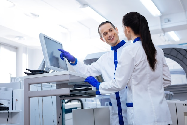 Flertando no trabalho. cientista bonito segurando a mão perto da tela e flertando com a cientista enquanto ela fica de costas