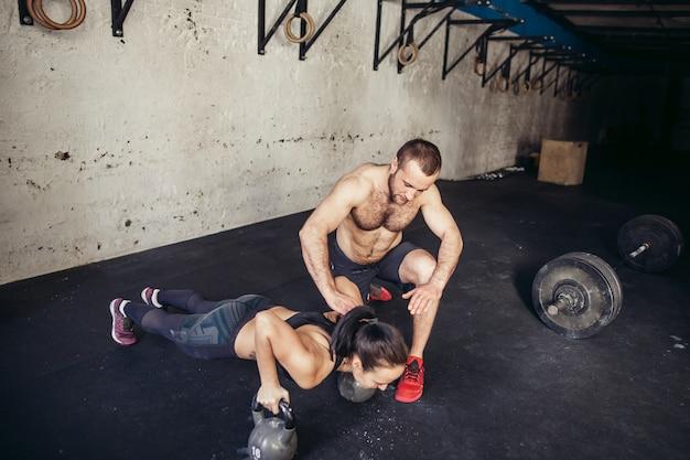Flexão de força de flexão de homem e mulher treinador em um treino de fitness