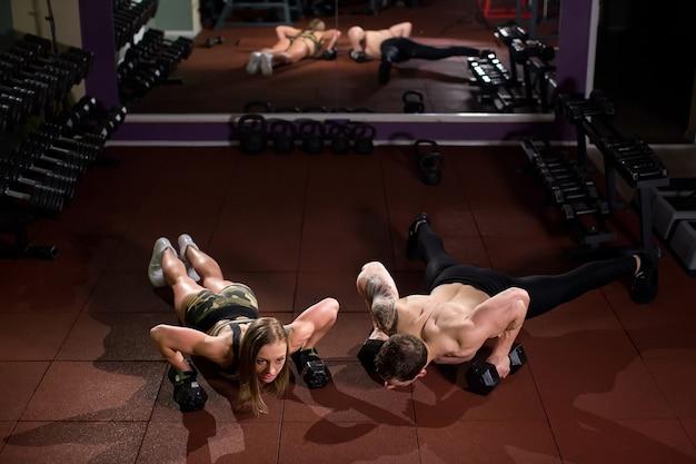 Flexão de força para homem e mulher na academia com halteres em um treino de fitness