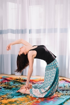 Flexível jovem fazendo yoga no ginásio