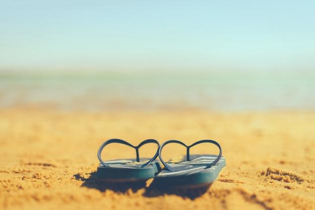 Flip-flop da marinha na praia amarela da areia com fundo azul do mar e do céu.