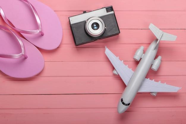 Flip-flops com uma câmera, avião em uma madeira rosa. conceito de viagens, turismo ou resort