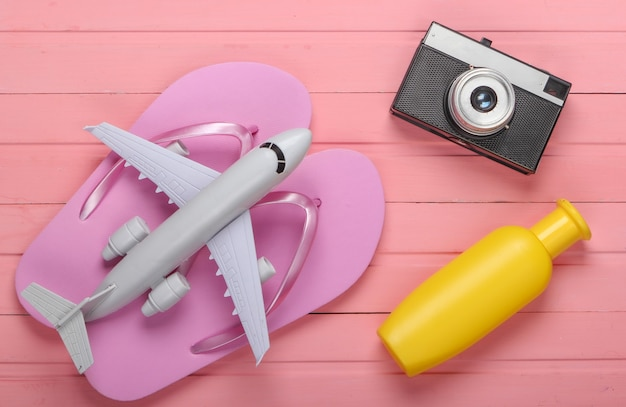 Flip-flops com uma câmera, avião, protetor solar em uma madeira rosa. acessórios de praia.