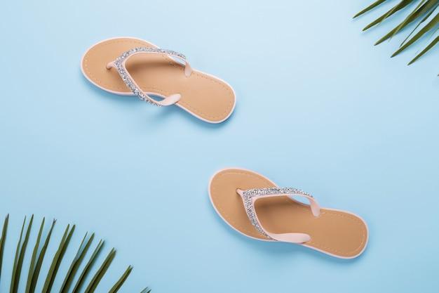 Flip-flops da praia da mulher bonita no fundo azul pastel claro. conceito de verão praia e conceito de férias, vista superior