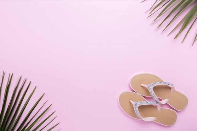 Flip-flops da praia da mulher bonita no fundo rosa pastel claro. conceito de verão praia e conceito de férias, vista superior