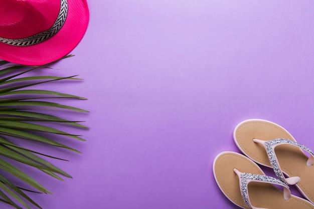 Flip-flops da praia da mulher bonita no fundo violeta ou roxo. conceito de verão praia e conceito de férias, vista superior