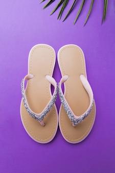 Flip-flops da praia da mulher bonita no violeta ou no roxo. conceito de verão praia e conceito de férias, vista superior