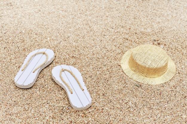 Flip-flops de praia e chapéu na praia de areia. acessórios de praia.
