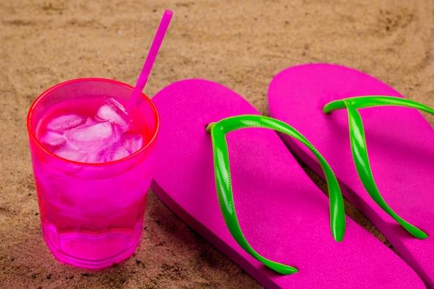 Flip flops e bebida gelada com gelo em uma praia de areia
