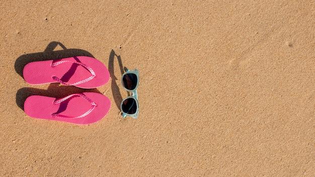 Flip flops e óculos de sol na areia