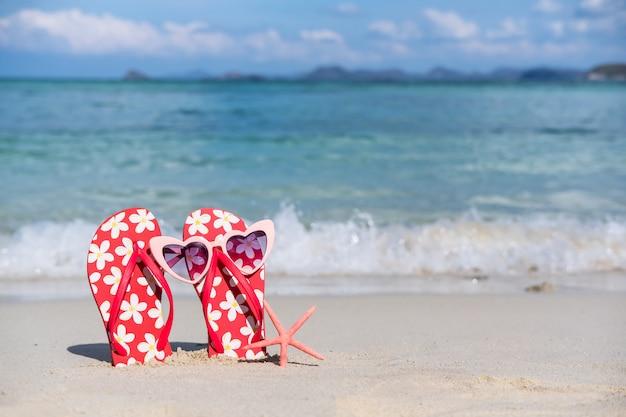 Flip-flops e óculos de sol na praia tropical arenosa branca, férias de verão e conceito de viagem