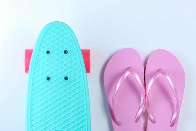 Flip-flops e placa de plástico mini cruiser em fundo branco. diversão de verão. vista do topo