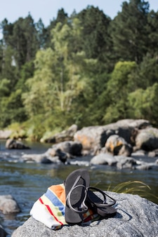 Flip flops e toalha na pedra perto da água