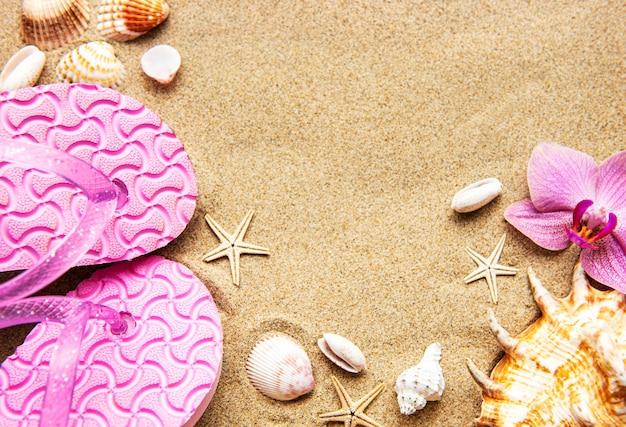 Flip-flops na areia com estrelas do mar e flores de orquídea