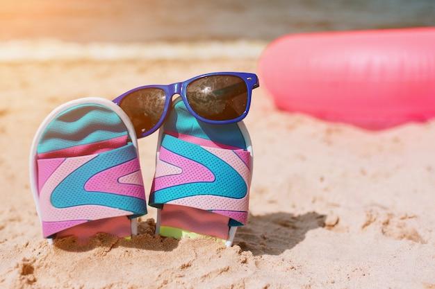 Flip-flops na areia na praia. óculos de sol nele. conceito de férias de verão. beira mar. paraíso. anel de natação rosa deitado atrás na areia.