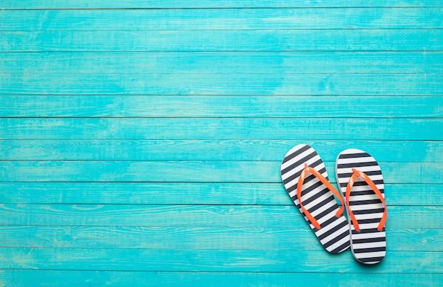 Flip-flops na cor de fundo de madeira
