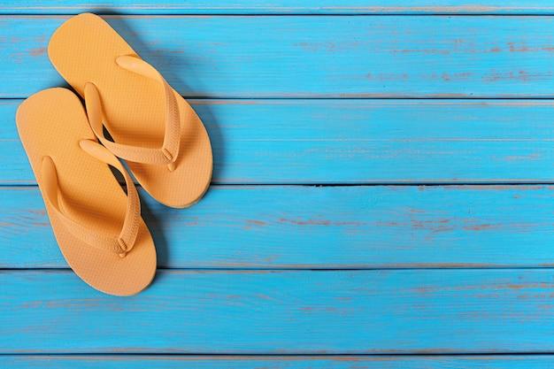 Flip flops na velha madeira de praia azul resistida