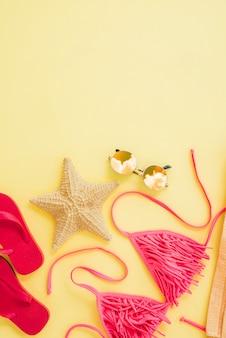 Flip flops perto da estrela do mar e maiô com óculos de sol